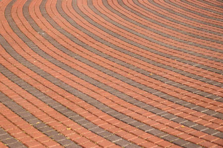 Round sidewalk pavers in red and grey