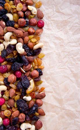 Obst liegen auf einem hellbraunen Blatt Papier getrocknet, all-Sorten, Nüsse verschiedener Typen, eine Feige, trockene Aprikosen, Datteln, Pflaumen, Preiselbeeren, Rosinen,