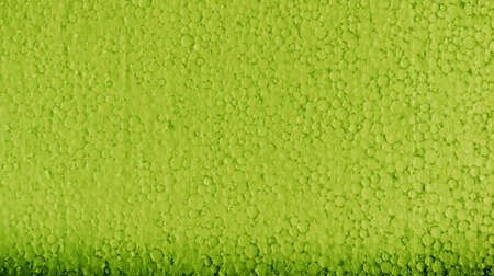 polyfoam: poly-foam the painted in green color, uneven surface, small drawing a circle, glints in the sun, the lower part of dark green color