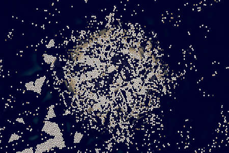 fragments: on a blue background bright yellow spot of flying small fragments with similar explosion Stock Photo
