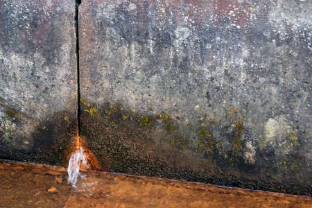 two concrete slabs of dirty gray color in spots, rusty water flows from the hole from below, in the foreground there is a liquid rusty from corrosion, a gloomy look, design, background, daylight,