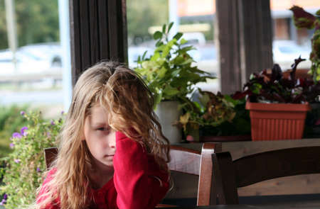little girl sits alone in a cafe, covered half of her face with her hand and blond hair, a red jacket, flowers in the background, a chair next to her, a tired and offended look,