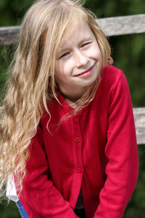 little blonde girl with curly long hair, portrait, in a red sweater in the sun, vertical photo, looks at the camera and smiles, in the background a wooden fence and green foliage, Banco de Imagens