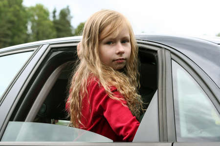 little girl with long blond hair and in a red jacket looks through the open window of the car into the camera, climbed out of the window to the waist, leaves, takes away, farewell look Banco de Imagens