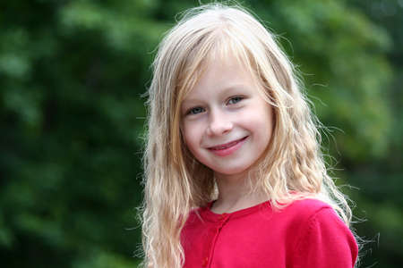 portrait little girl with long blond hair in a red sweater smiling and looking directly at the camera, in the background green trees, dark foliage,