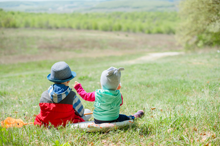 Little boy and baby girl sitting on a background of green landscape.