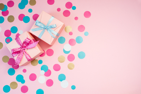 Decorated boxes and confetti on the pink background. Stok Fotoğraf