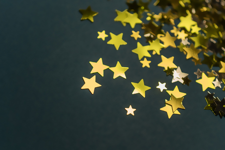 Golden confetti stars scattered on the surface.