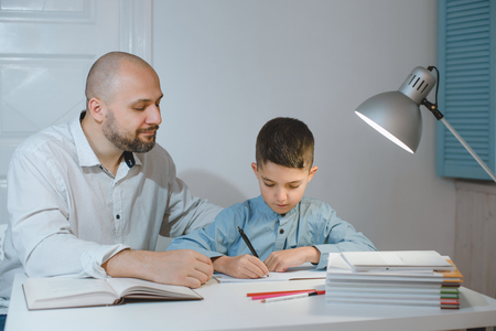 Father and son work together on school homework or homeschooling. Banco de Imagens