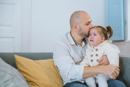 The toddler girl cries in her fathers arms.