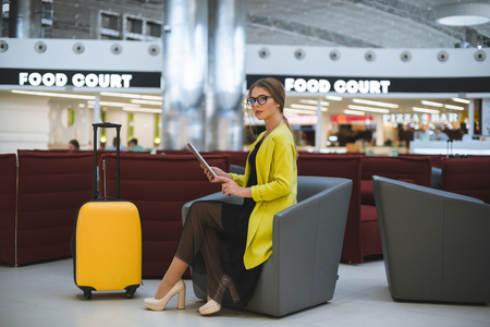 Young beautiful business woman in the airport lounge uses a smartphone and tablet.