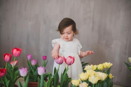Beautiful smiling baby girl among the tulips.