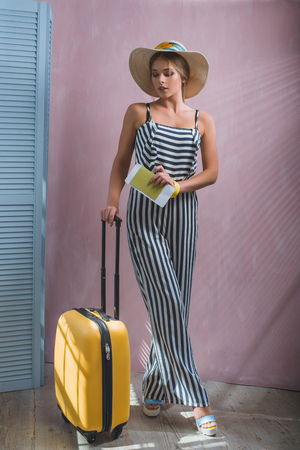 Young stylish Caucasian woman at the airport with a yellow suitcase and a straw hat.