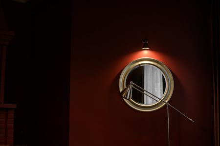 Frammento dell'interno in modo oscuro: uno specchio rotondo in una cornice massiccia e una lampada da terra.