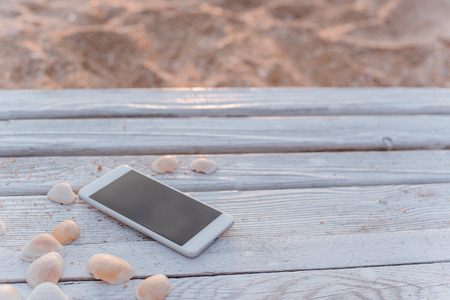 The smartphone lies in the encircling of seashells on wooden boards. Stock fotó