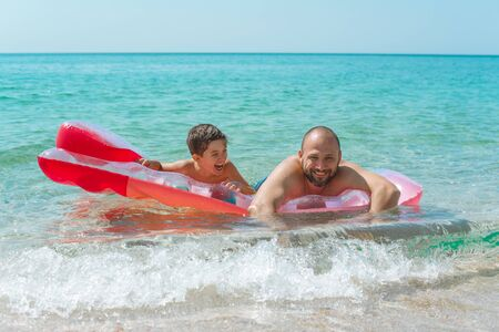 A happy father and son swim on an inflatable mattress on a sunny summer day.