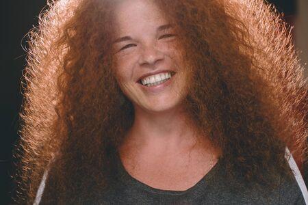 Retrato de mujer étnica pelirroja de pelo rizado con pecas. Foto de archivo