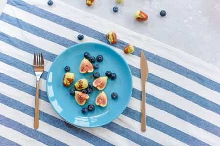 Fresh, ripe figs and jujube on a blue plate.