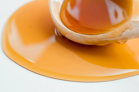 Thick honey of saturated color drips from a wooden spoon.