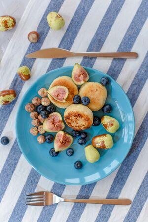 Fresh cheese pancake, ripe figs, jujube, blueberry and raw hazelnuts on a blue plate.