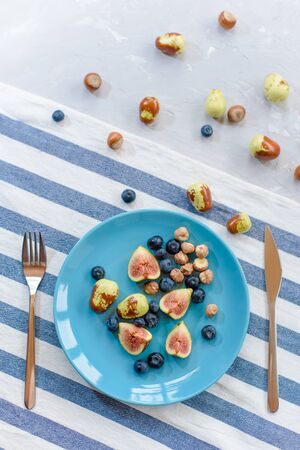 Fresh, ripe figs, jujube, blueberry and raw hazelnuts on a blue plate. Reklamní fotografie