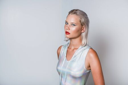 Attractive young blonde in a holographic silver hoody bodysuit. Reklamní fotografie