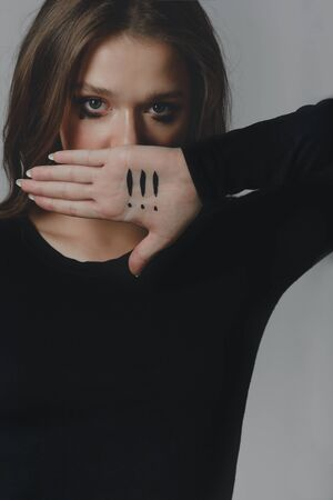 A crying young girl covering her mouth with her palm, on which there are three exclamation marks.