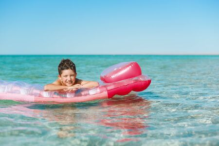 Cheerful boy swims in the sea on a inflatable mattress.