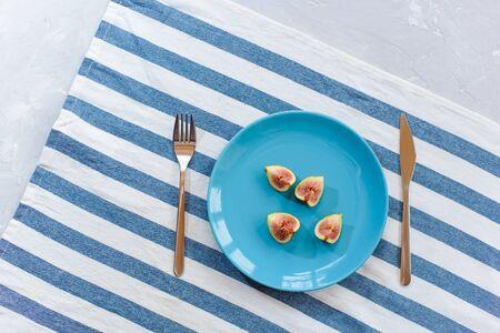 Fresh, ripe figs on a blue plate.
