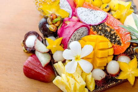 Juicy ripe tropical Thai fruits on a wooden dish. Stock Photo