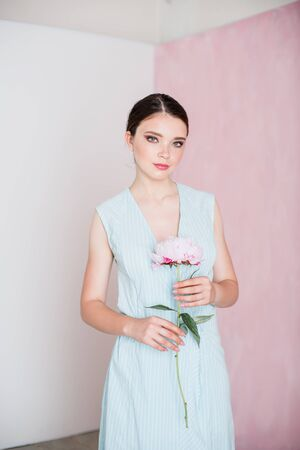 A young woman with gathered hair is standing holding a peony in her hands.