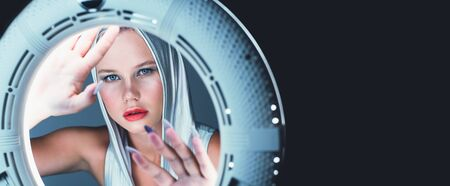 Attractive young blonde looks like in the porthole of a spaceship. Futuristic portrait. Banque d'images