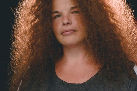 Portrait of ethnic redhead curly-haired woman with freckles.