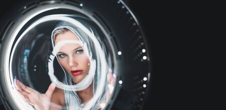 Attractive young blonde looks like in the porthole of a spaceship. Futuristic portrait. Banque d'images - 132315836