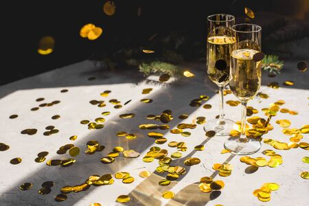 Two glasses of champagne in golden confetti.