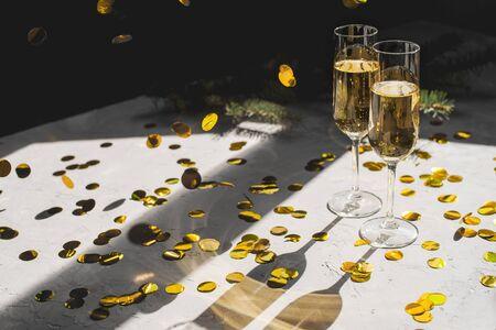 Two glasses of champagne in golden confetti.