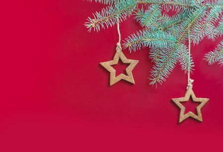 Golden wooden stars, Christmas toys, hung on a spruce branch on jute ropes on a red background. Christmas photo.
