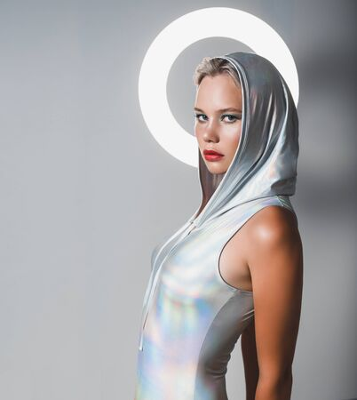 Attractive young blonde with a hood and a halo over her head.