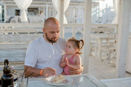 A father feeding with a spoon his little daughter while sitting at a table in a summer cafe by the sea. Zdjęcie Seryjne