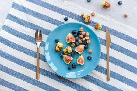 Fresh, ripe figs, jujube, blueberry and raw hazelnuts on a blue plate. Stock fotó