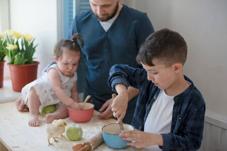 Dad with his little son and daughter baking together. Stok Fotoğraf
