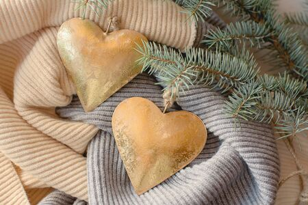 Two Christmas toys, golden hearts on jute ropes and a branch of blue spruce.