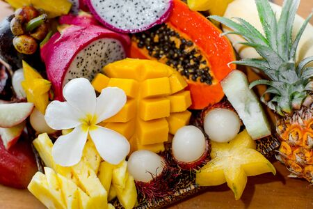 Juicy ripe tropical Thai fruits on a wooden dish. Stok Fotoğraf