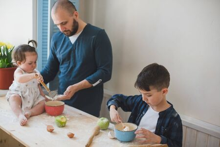 Cropped photo dad with his little son and daughter baking together.