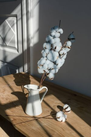 A bouquet of cotton in a white jug on a wooden table.