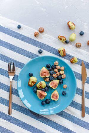 Fresh, ripe figs, jujube, blueberry and raw hazelnuts on a blue plate. Stok Fotoğraf