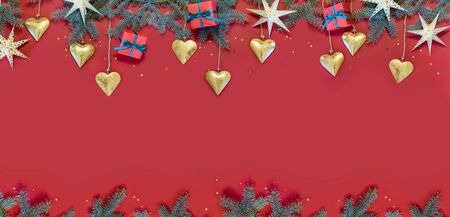 Image of a bright Christmas decor on a red background and branches of spruce.