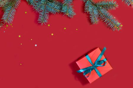 Image of beautiful red gift boxes and spruce branches on a red background.