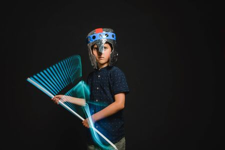 A kid with a lightsaber in his hands play in a superhero battle.