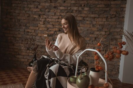 A young attractive woman sits in a chair with a smartphone in her hands. Reklamní fotografie